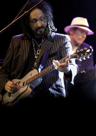 Mike Campbell on guitar, Benmont Trench in the background.